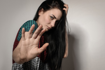 Young woman making stop gesture against light background, focus on hand