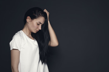 Portrait of upset young woman on dark background. Space for text