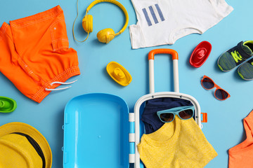 Flat lay composition with child suitcase and accessories on blue background