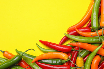 Canvas Prints Hot chili peppers Different hot chili peppers on yellow background, flat lay. Space for text