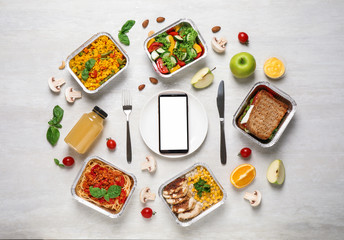 Flat lay composition with lunchboxes and smartphone on white wooden table, mockup for design. Healthy food delivery
