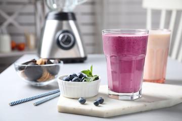 Tasty milk shake and blueberries on white table