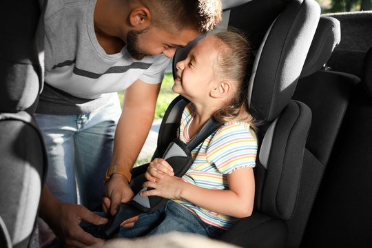 Father fastening his daughter with car safety seat belt. Family vacation