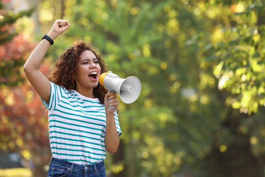 Angry African-American woman with megaphone outdoors. Protest leader