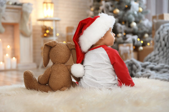 Little baby with Santa hat and toy on floor at home. First Christmas