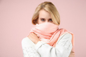 Beautiful woman wearing warm scarf on pink background. Autumn clothes