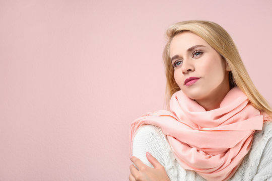Beautiful woman wearing warm scarf on pink background, space for text. Autumn clothes