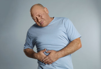 Obraz Mature man suffering from liver pain on light grey background - fototapety do salonu