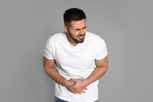 Man suffering from abdominal pain on light grey background