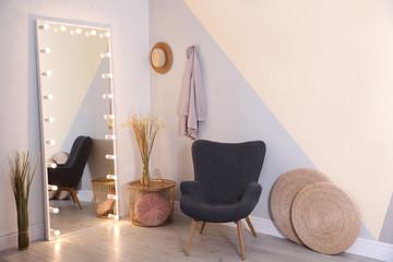Large mirror with lamps in stylish room interior