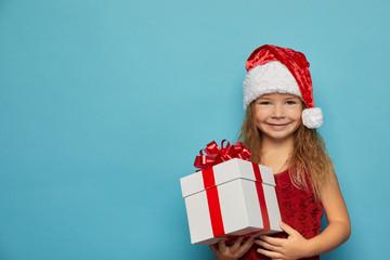 Girl in Santa red hat holding Christmas gift