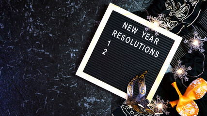 New Year's Eve resolutions flatlay with letter board and black and gold party decorations with negative copy space.