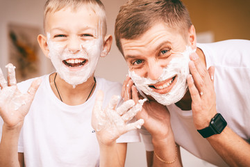 Man and little boy with shaving foam on their faces looking into the bathroom mirror and laughing....