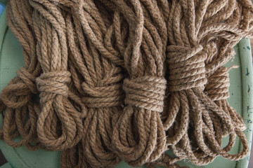 Set of organic fiber ropes tied off into individual lengths and set in a pile