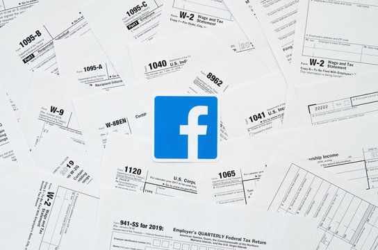 Printed Facebook logo on many tax form blanks lies on table close up. Help with tax problems using internet and information from social networks