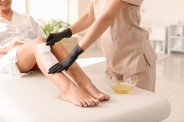 Young woman undergoing epilation of legs in beauty salon
