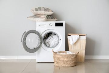 Obraz Modern washing machine with laundry near white wall - fototapety do salonu