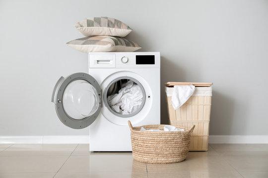 Modern washing machine with laundry near white wall