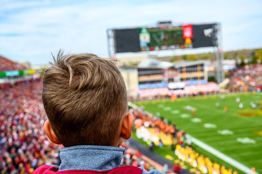 young boy looking at blurred background of football game