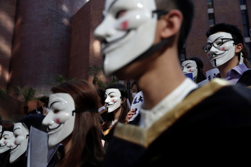 University students wearing Guy Fawkes masks pose during a news conference to support anti-government protests before their graduation ceremony at the Hong Kong Polytechnic University in Hong Kong