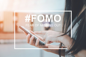 FOMO, fear of missing out concept. Close-up image of woman hand using mobile smartphone