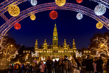 The Illuminating gate in front of the Christmas market by City hall -  Rathaus in night Vienna,...