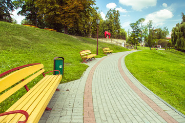 Beautiful park with an alley and benches and a green meadow.  Blue sky with clouds, grass and trees