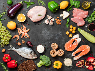Mediterranean diet concept with copy space in center. Top view of selective food ingredients of Mediterranean Diet on dark background. Flat lay.