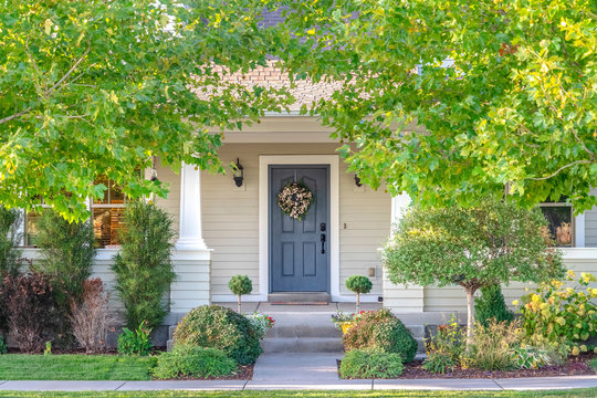 Front door of a home surrounded by leafy trees