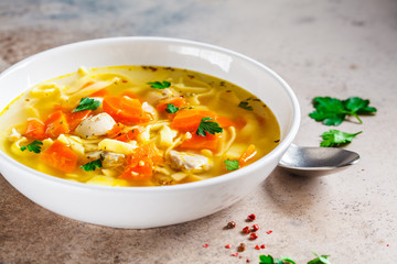 Chicken soup with noodles, parsley and vegetables in a white plate.