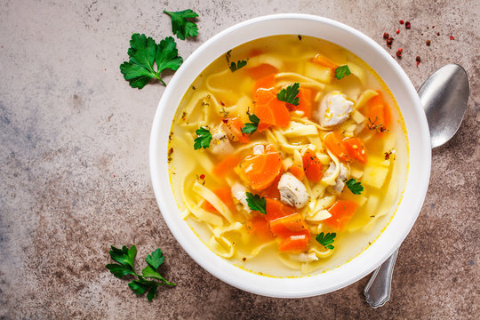 Chicken noodle soup with parsley and vegetables in a white plate, top view.