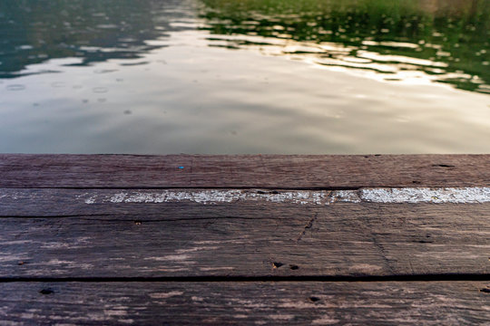 Empty wood floor with shimmering surface,Empty old wooden pier with ripple of lagoon water,Wooden desk over blue sea background vintage tone