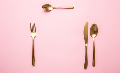 Gold cutlery set against pink background, formal place setting