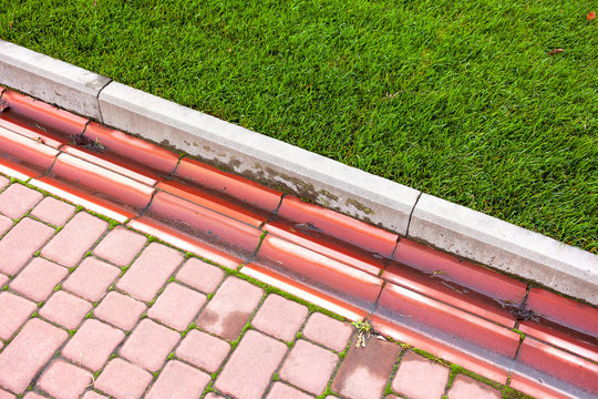 Drainage system in the park by the green lawn and footpath of red paving slabs.