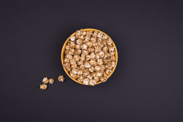 Caramel sweet popcorn bowl isolated on black background top view. Top view, copy space, flat lay