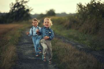 Foto op Plexiglas Artist KB Two adorable boys running on the country road