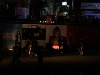 Iraqi demonstrators light candles during the ongoing anti-government protests in Baghdad