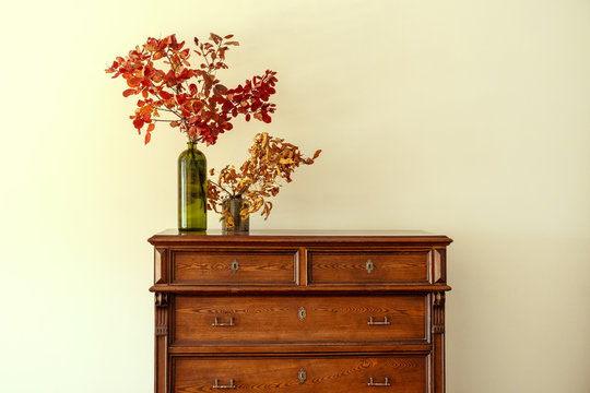 Wooden chest of drawers with floral branches in vase