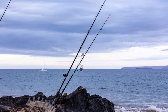 Fishing rods in a white stands on a side of a black rock against an ocean, Maui, Hawaii