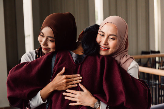 Cheerful Asian female in traditional Islamic hijabs smiling and embracing friend of different religion during meeting