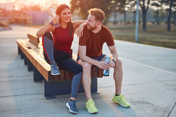 Modern couple making pause in an urban park during jogging / exercise.
