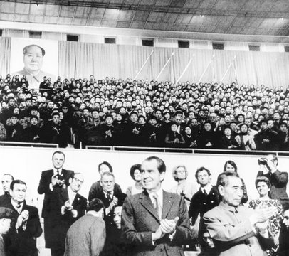 President Richard Nixon and Premier Chou En-lai applaud Chinese athletes prior to a gymnastic performance at the Capital Gymnasium