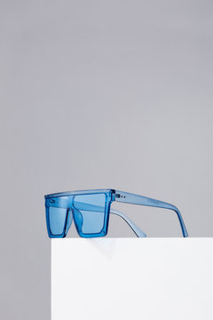 Subject shot of square oversized sunglasses with thick bluish frame and blue lenses. The sunglasses are isolated on the white square on the gray background.