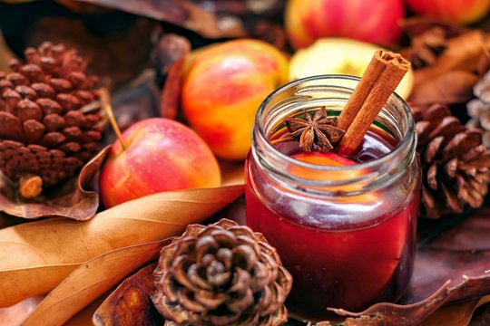 Autumn sangria with apples and cinnamon, autumn leaves brown color background with pinecone, holiday wine cocktail drinking, copy space