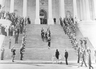 Jacqueline Kennedy escorts her children, Caroline and John, Jr. up the steps of the Capitol