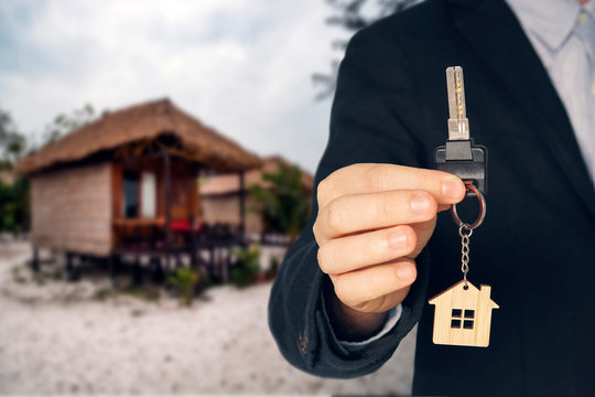 Rent a Bungalow on the beach for a holiday. man buying new house. hand receiving house key. Close up hand holding house key.