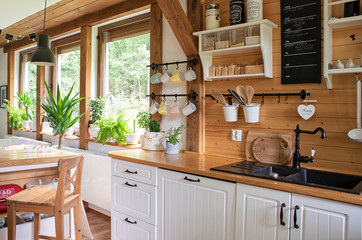 Interior of kitchen in rustic style with vintage kitchen ware and window. White furniture and wooden decor in bright indoor. Country style.