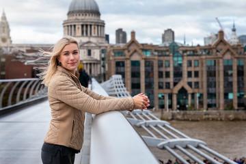 Eine hübsche, blonde Touristin in London steht vor der St. Pauls Kirche und geniesst ihren Sightseeing Trip durch die Stadt