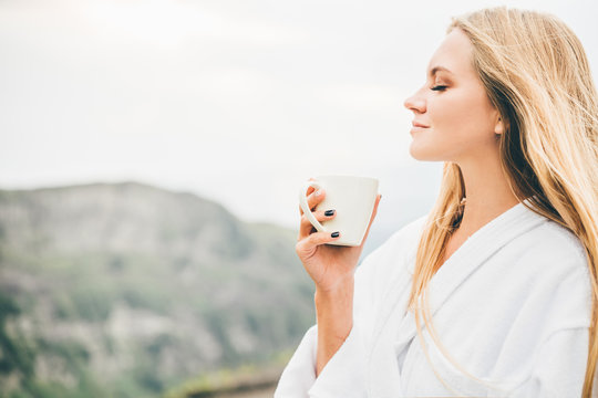 Side view woman in SPA bathrobe standing in the beautiful mountain view at the sunset. Travel and healthy lifestyle and beauty outdoors.