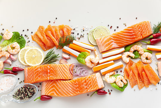 fresh seafood on a table with spices, vegetables and olive oil: fresh and smoked salmon, shrimp and crab sticks for a supermarket or fish sushi restaurant.
